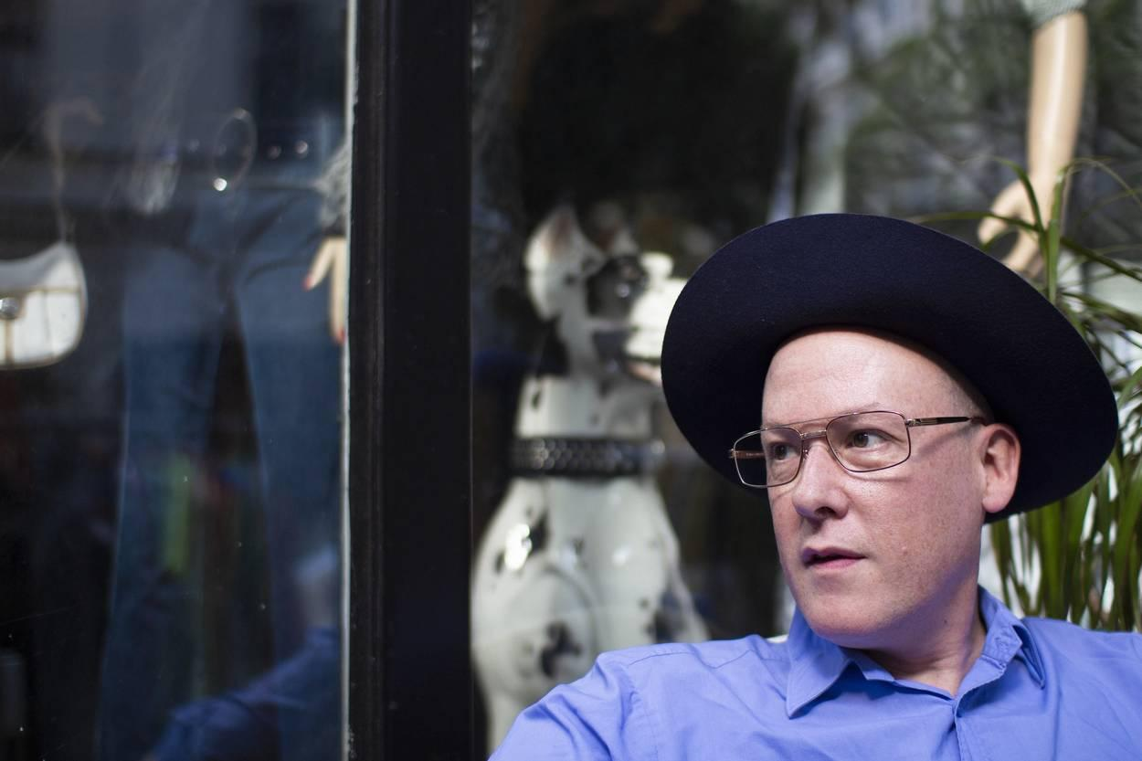 Person mit Hut sitzt vor einer Glastür in der sich etwas spiegelt Pressefoto hearthemusic