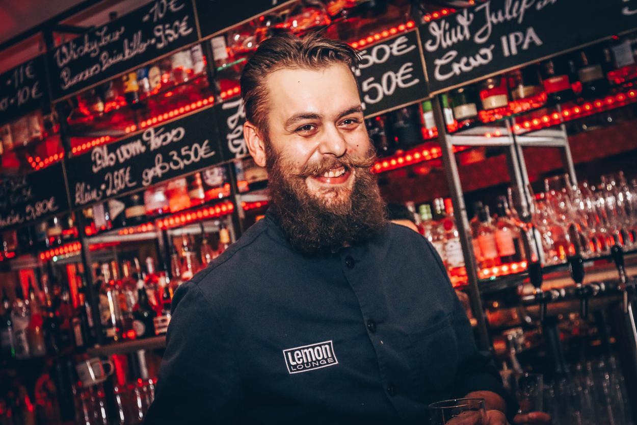 Lemonlounge Barkeeper steht lachend vor der Bar